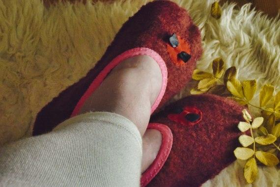 Kuvassa on punaiset aamutohvelit naisen jalassa.
