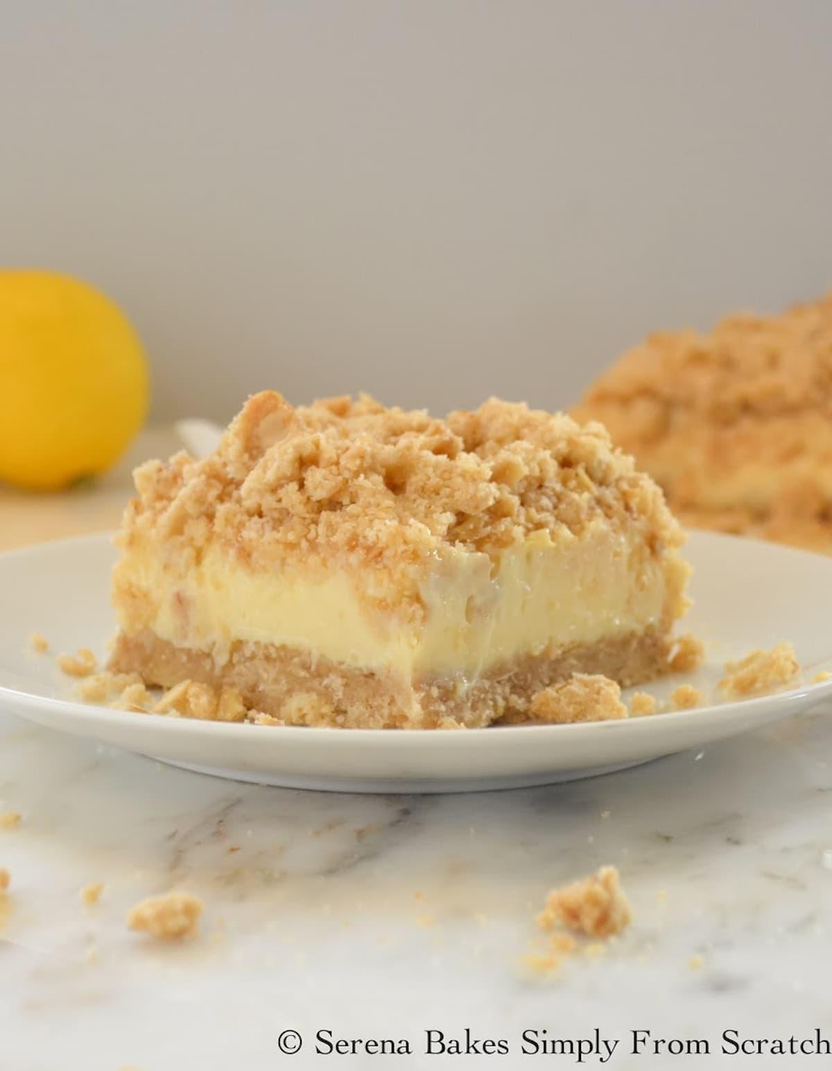 Sliced Lemon Cheesecake Crumb Bars on a white plate with a pan of Lemon Cheesecake Crumb Bars in the background.