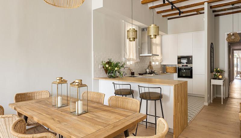Cocina con barra de madera abierta al salón