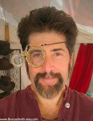 Brass metal steampunk monocle with articulated magnifying lens that opens and closes. Steampunk metal mask or eyepatch