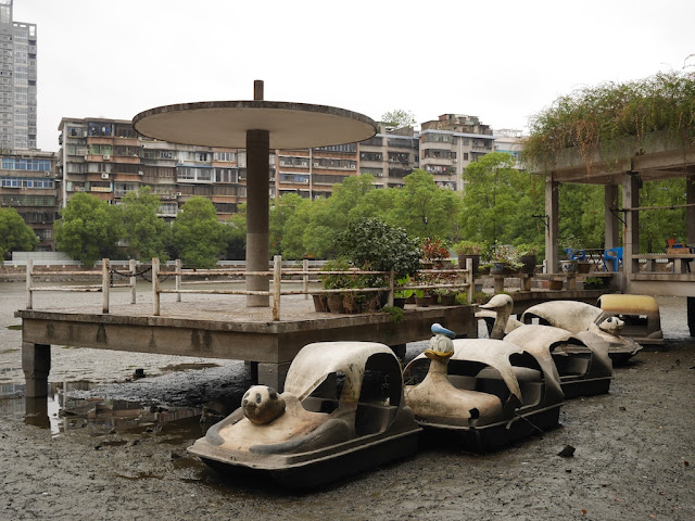 character-themed pedal boats sitting in a drained pond in Hengyang