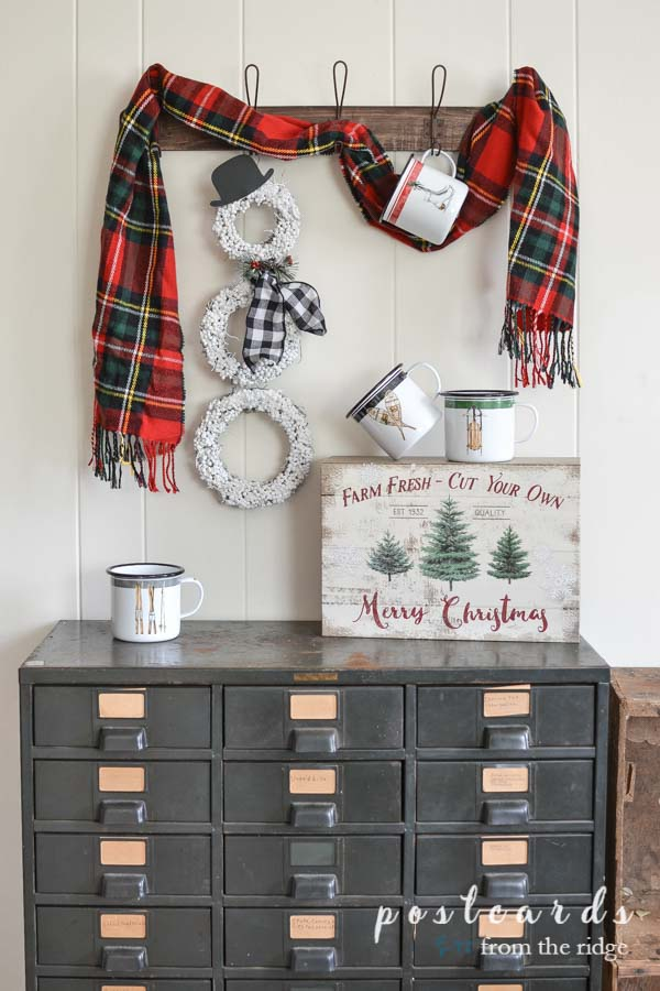 snowman wreath and red plaid scarf with winter snow equipment enamel mugs