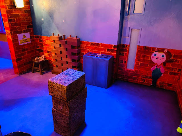 A pile of pretend hay bricks in a dark room with a wall of bricks