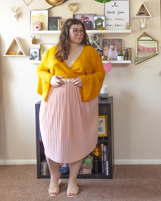 An outfit consisting of a yellow wrap dress with a deep neckline, tucked into a pink pleated midi skirt and pink slide sandals.