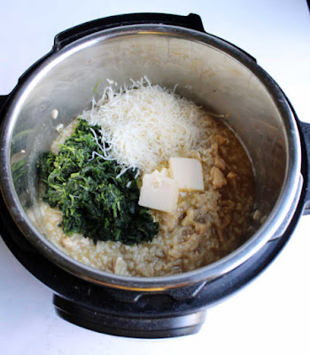 instant pot of freshly made risotto with shredded spinach, cheese and pats of butter on top ready to be stirred in