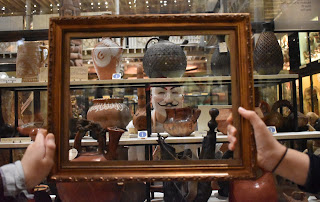 Young person standing next to Pitt Rivers Museum case wearing the V for Vendetta mask made famous in the Occupy protests