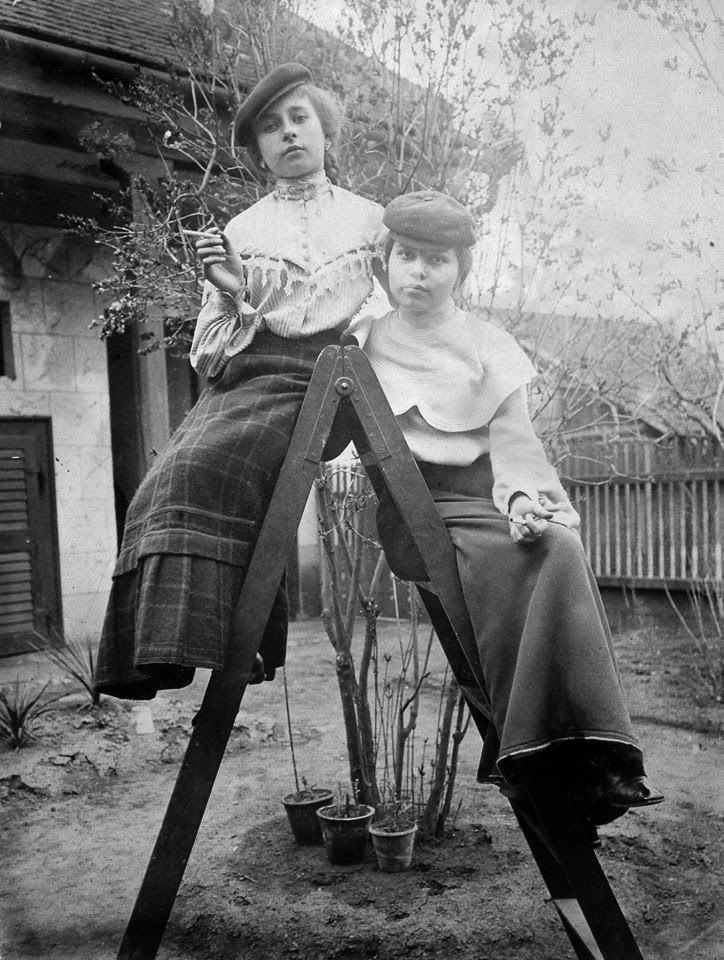 Fortepan-fotó két Karády Katalin stílusában cigarettázó lányról, akik egy létrán ülnek hosszú szoknyában és micisapkában, a háttérben kerítés.