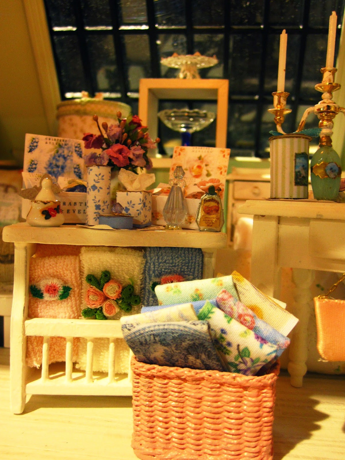 Modern miniature shabby chic shop display of sheets towels, cake stands and toiletries on cream shelves.