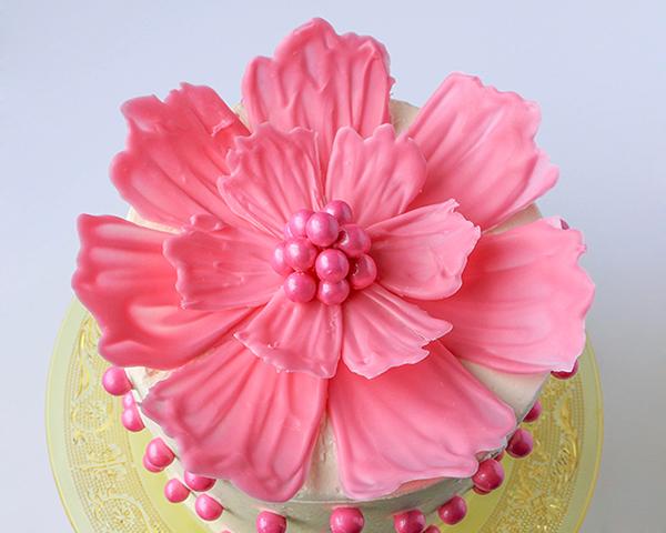 Τα ίδια ζαχαρωτά μπορείτε να χρησιμοποιήσετε για να γεμίσετε το κέντρο, αλλά και να τα ρίξετε γύρω από την τούρτα ή το κέικ ή να τα κολλήσετε περιμετρικά για ένα αρμονικό αποτέλεσμα. Φτιάξατε τέλεια λουλούδια για τούρτες!