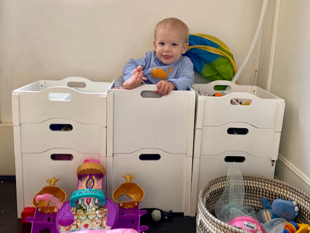 one year old boy sitting in a white stacking toy box in his pyjamas