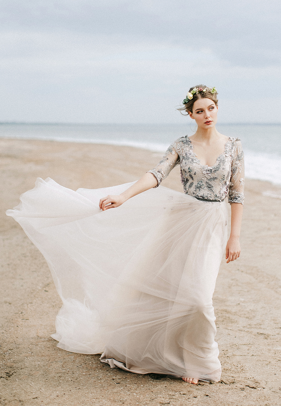 This stunning grey lace wedding dress is just one of many wedding dresses from She Wore Flowers. Angellure creates this wedding gown with a tulle skirt and delicate long lace sleeves.