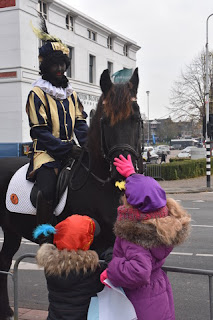 Children petting a horse bearing a costumed rider, Zaandam, The Netherlands