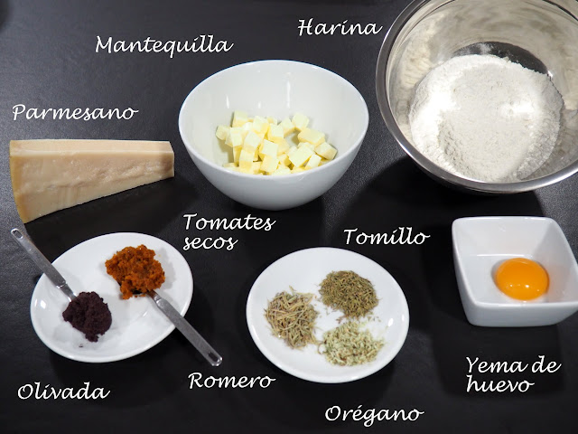 Galletas saladas para aperitivo, con queso parmesano, tomates secos, olivas negras, tomillo, romero y orégano.