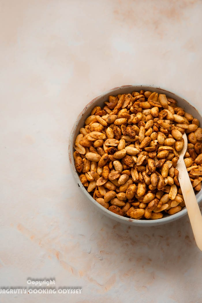 A bowl full of mexican flavoured air fryer roasted peanuts with a spoon.
