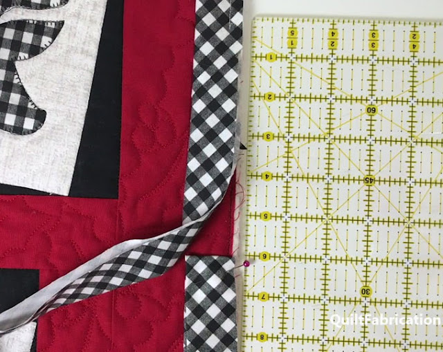black and white check binding stitched to a quilt
