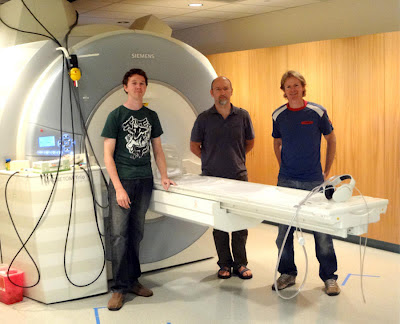 Part of the research team in front of the Magnetic Resonance Imaging (MRI) device at the UCSB Brain Imaging Center From left to right : Researcher Tim Preston; Associate Professor of Psychological & Brain Sciences Barry Giesbrecht; and Professor of Psychological & Brain Sciences Miguel P. Eckstein. Not pictured: Koel Das, now a faculty member at the Indian Institute of Science in Bangalore, Karnatka, India; and lead author Fei Guo, now in the software industry.