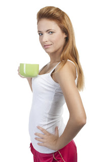 Young redhead woman on white background with a green cup of tea or coffee