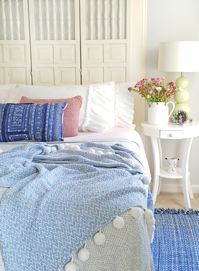 bed with pom pom throw blanket and blue, pink and ruffled pillows