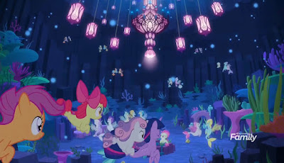 Twilight and the Crusaders, entering from bottom left, swim into a mostly navy blue Seaquestria. There are lamps hanging from the ceiling and several seaponies in the distance