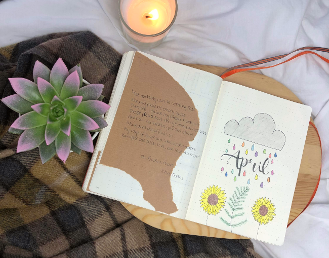 Open journal with the word april written between a cloud and some sunflowers