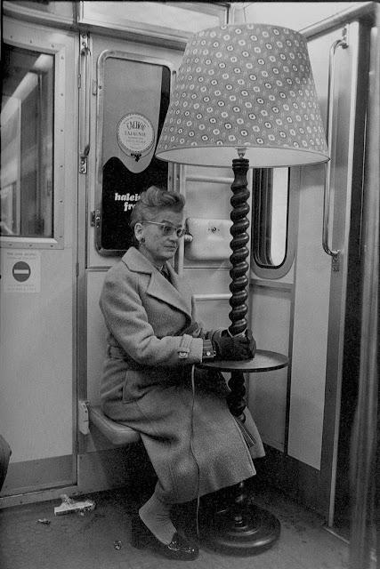 Elderly woman sat next to combination lamp on subway train