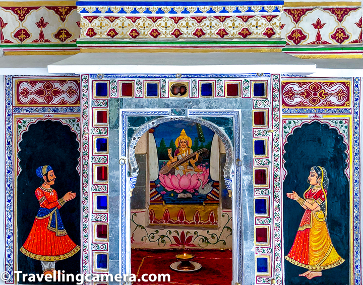 Above photograph shows relatively new art around the main door of the section where multiple musical instruments are placed inside Udaipur City Palace. The art shows Ma Saraswati in the middle and a man/woman praying in front of her. There is also a lamp in front of Ma Saraswati painting.