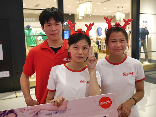 two young women wearing deer antlers and one young man at a Coca-Cola promotion in Bengbu, China
