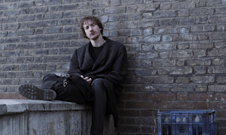 Still from the film Naked - David Thewlis sitting on a wall
