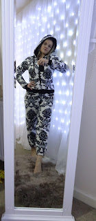 woman taking self in mirror wearing white and black onesie