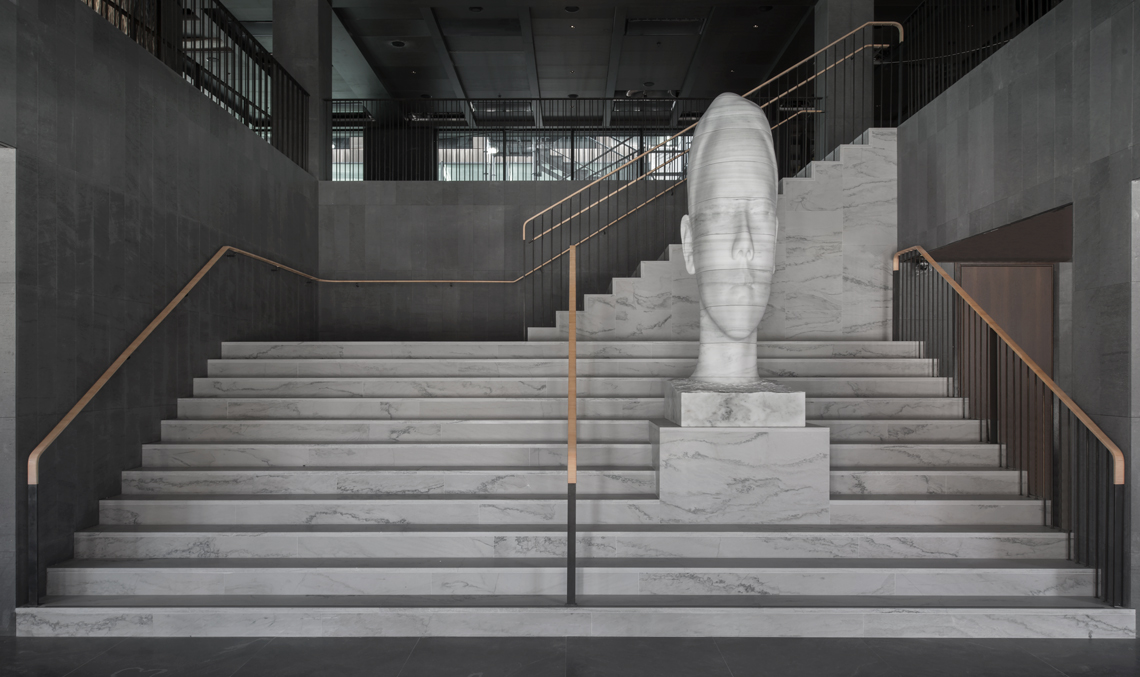 Magnificent marble bust on steps in Six Hotel in Stockholm, Mar Whispering by Jaume Plensa