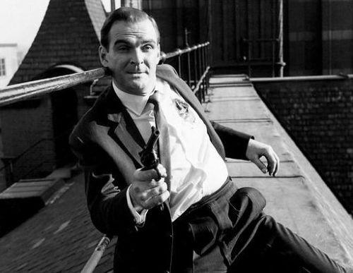Stanley Baker on a rooftop holding a gun