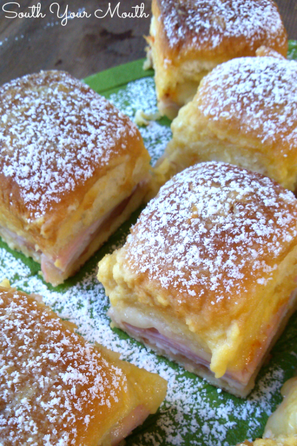 Monte Cristo Party Sliders! Party appetizer sandwiches made with ham, turkey and cheese baked in a buttery topping dusted with powdered sugar just like the classic Monte Cristo!