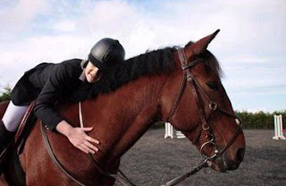 A rider hugging her bay horse while on his back
