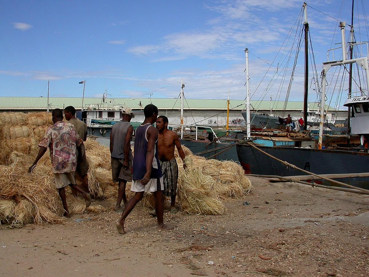 des hommes chargent un bateau dans le port aux boutres