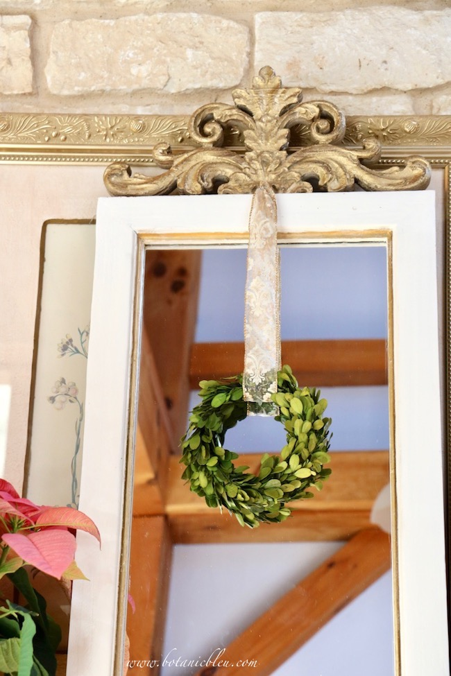 French country mirror decorated for Christmas by hanging a gold and white ribbon from a brass nail tapped into the top of the mirror