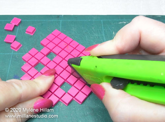 Square of pink pixels being trimmed with a craft knife to the shape of a space invader