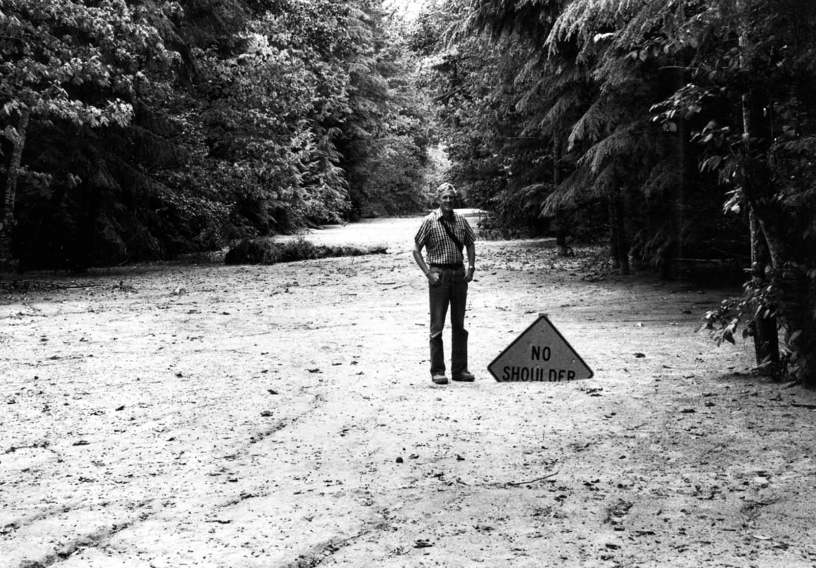 A solidified mudflow covers State Highway 504 near the town of Toutle, northwest of Mount St. Helens, to a depth of 2 m (6 ft). Geologist for scale.