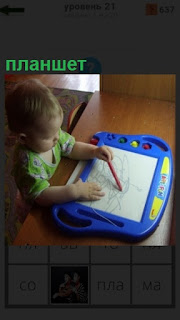 за столом сидит ребенок и рисует на планшете