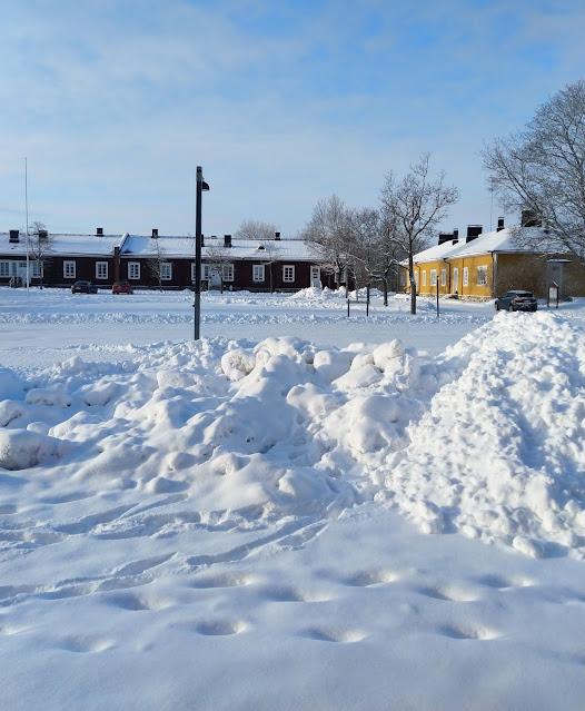 Luminen aukio, jonka laidalla on puisia rakennuksia.