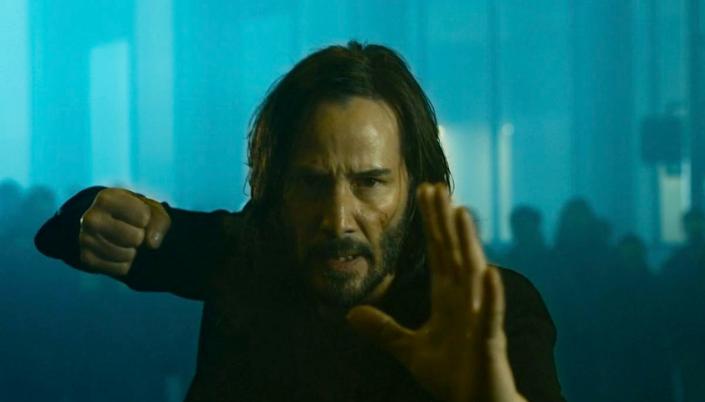 Imagem: o personagem Neo, interpretado por Keanu Reeves, um homem branco com longos cabelos pretos e barba por fazer, o rosto um pouco sujo e com sangue, vestindo um terno preto e numa pose de luta e cercado por várias pessoas em uma rua escura.