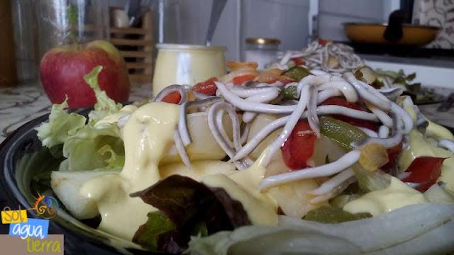 Fotografía de un plato de ensalada templada de verano con manzana, gulas y salsa de mostaza y yogur