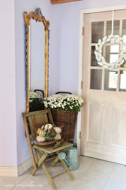 French Country rustic fall entry with elegant French mirror juxtaposed against a rustic wooden folding chair