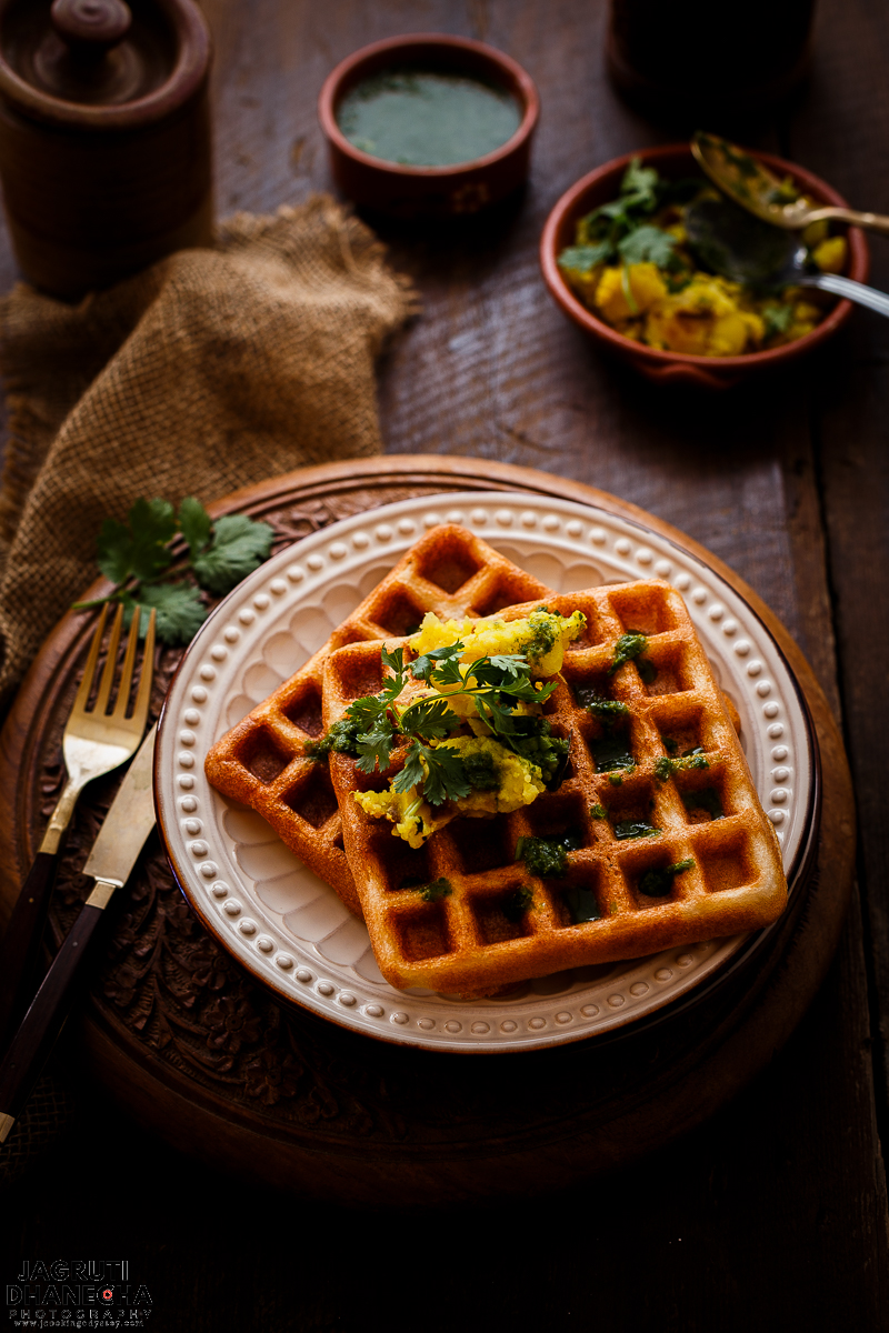 Waffle Idli Delight is a savoury, fluffy and crispy waffle prepared with traditional Idli batter and served with mildly spiced potato filling and green chutney.