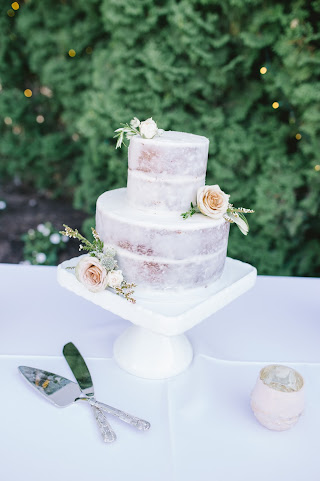 classic nearly naked cake adorned with white and beige blooms for a white garden wedding in utah