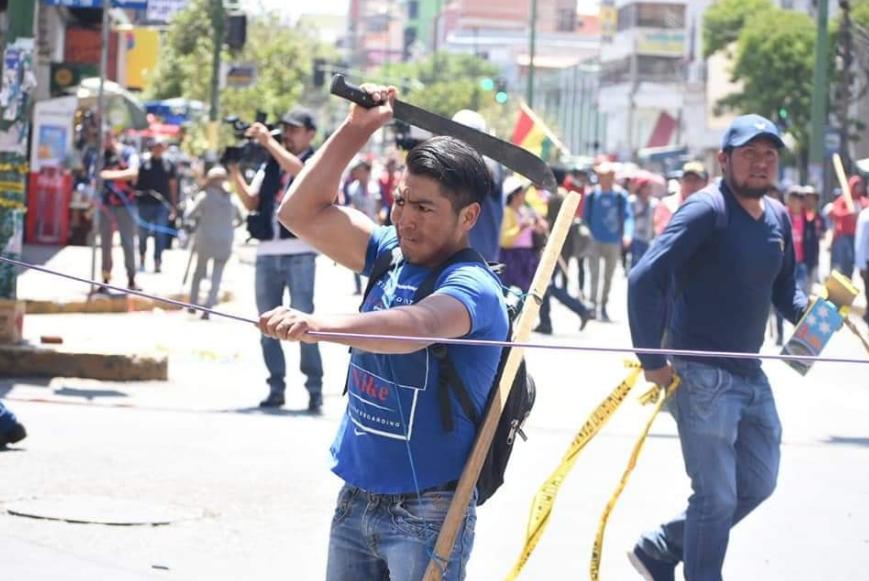 Manifestante del MAS con machete en mano corta una cinta puesta en el bloqueo vecinal de Cochabamba / FACEBOOK