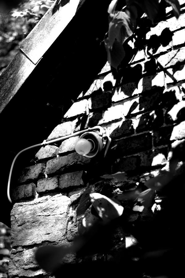 Blog + Fotografie by it's me! | fim.works | SchwarzWeissBlick No 17 | verlassenes Gehöft | Lost Place | Steinmauer mit Glühbirne ohne Schirm