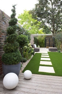 A narrow garden with white orbs and decorative trees in large urns.The seating area is to the rear past large white paving stones.