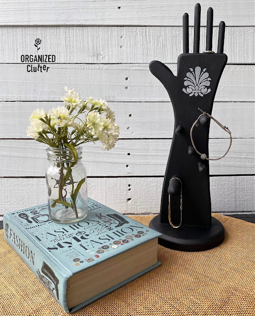 Photo of a stenciled black wooden hand shaped jewelry holder