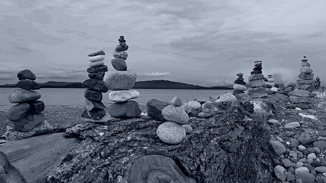 Stone totems adorn Parksville beach driftwood...