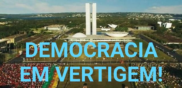 A foto mostra a Brasilia a Capital Federal do Brasil. No fundo o Congresso Nacional e a frase democracia em vertigem.